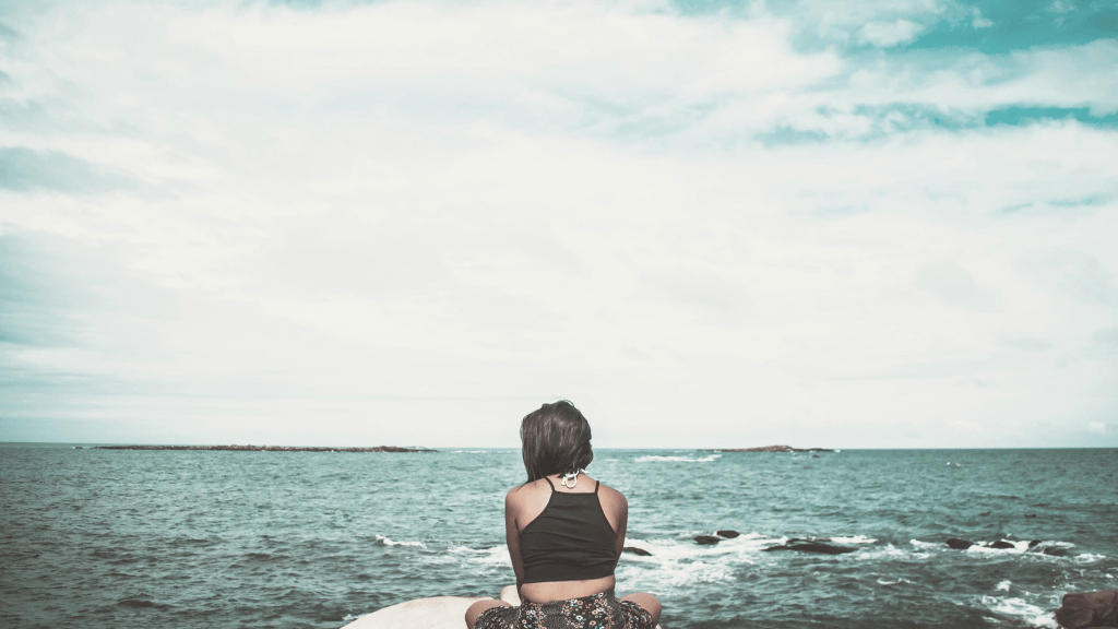 woman sitting with her back to us, singing towards the ocean
