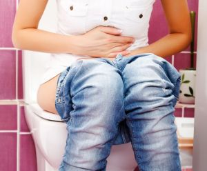 Woman with belly pains, sitting on the toilet.