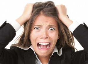 Woman screaming and pulling on hair with stress.