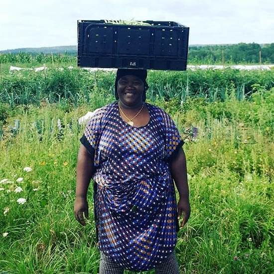 Liberation Farms worker balancing produce on her head
