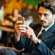 Erfolgreicher Geschäftsmann schaut auf sein Smartphone