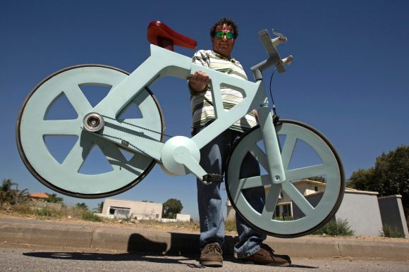 Israeli inventor Izhar Gafni holds his cardboard bicycle in Ahituv