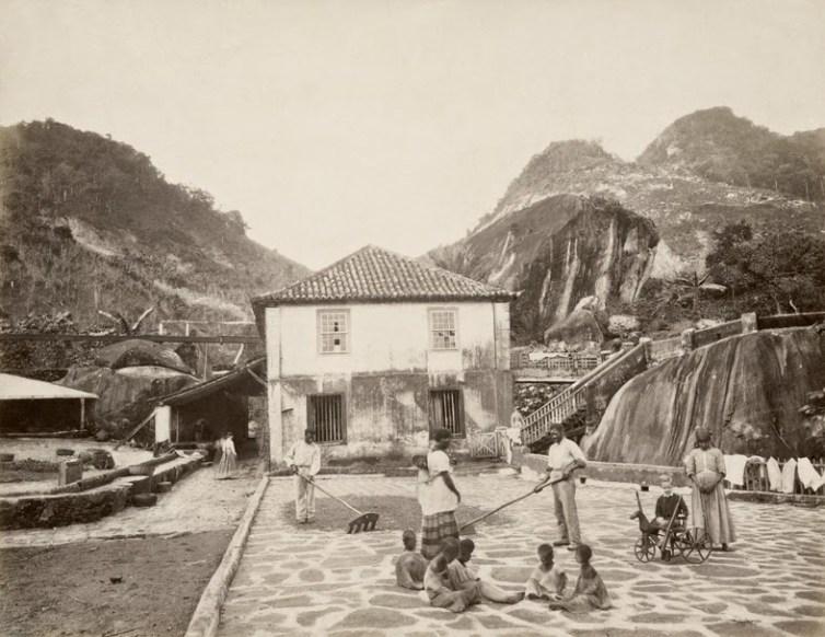 Foto da Fazenda Quititi, no Rio de Janeiro, 1865. Observe o impressionante contraste entre a criança branca com seu brinquedo e os pequenos escravos descalços aos farrapos (Georges Leuzinger_Acervo Instituto Moreira Salles)