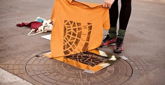 Coletivo de arte estampa camisetas nas ruas, em bueiros e ralos