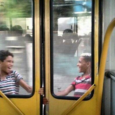 Dois garotos pendurados na porta do ônibus