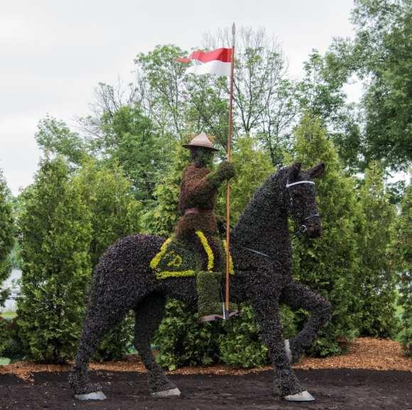 Cavaleiro em cima do cavalo segurando uma bandeira