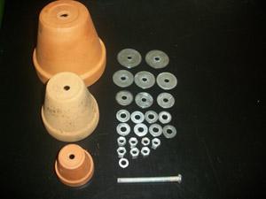 Três vasos de cerâmica, discos de metal de vários tamanhos e um pino de metal