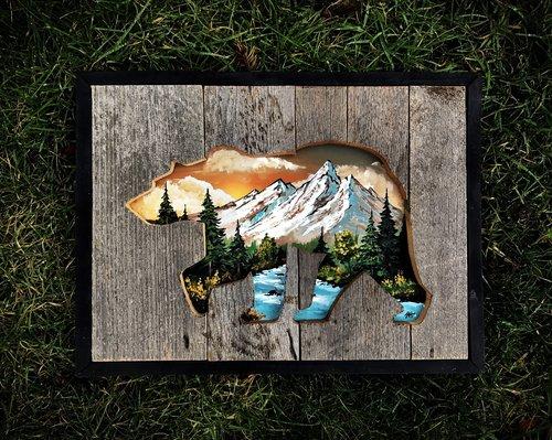 Urso vazado com paisagem de montanha, lago e pinheiros
