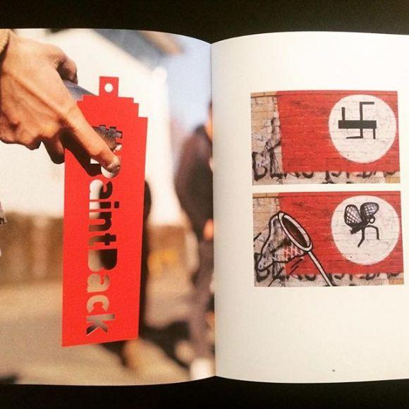 Livro aberto com foto de stencil #PaintBack e da mosca adaptada da suástica