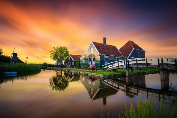 Casa antiga com moinho de vento e ponte de madeira