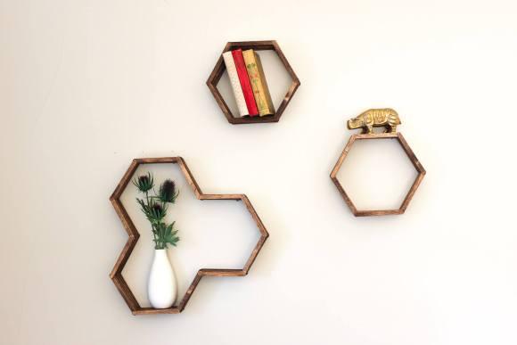 Estantes de colmeia e de hexágono na parede com livros e vasos