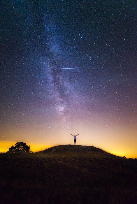 Via Láctea com cometa e pessoa