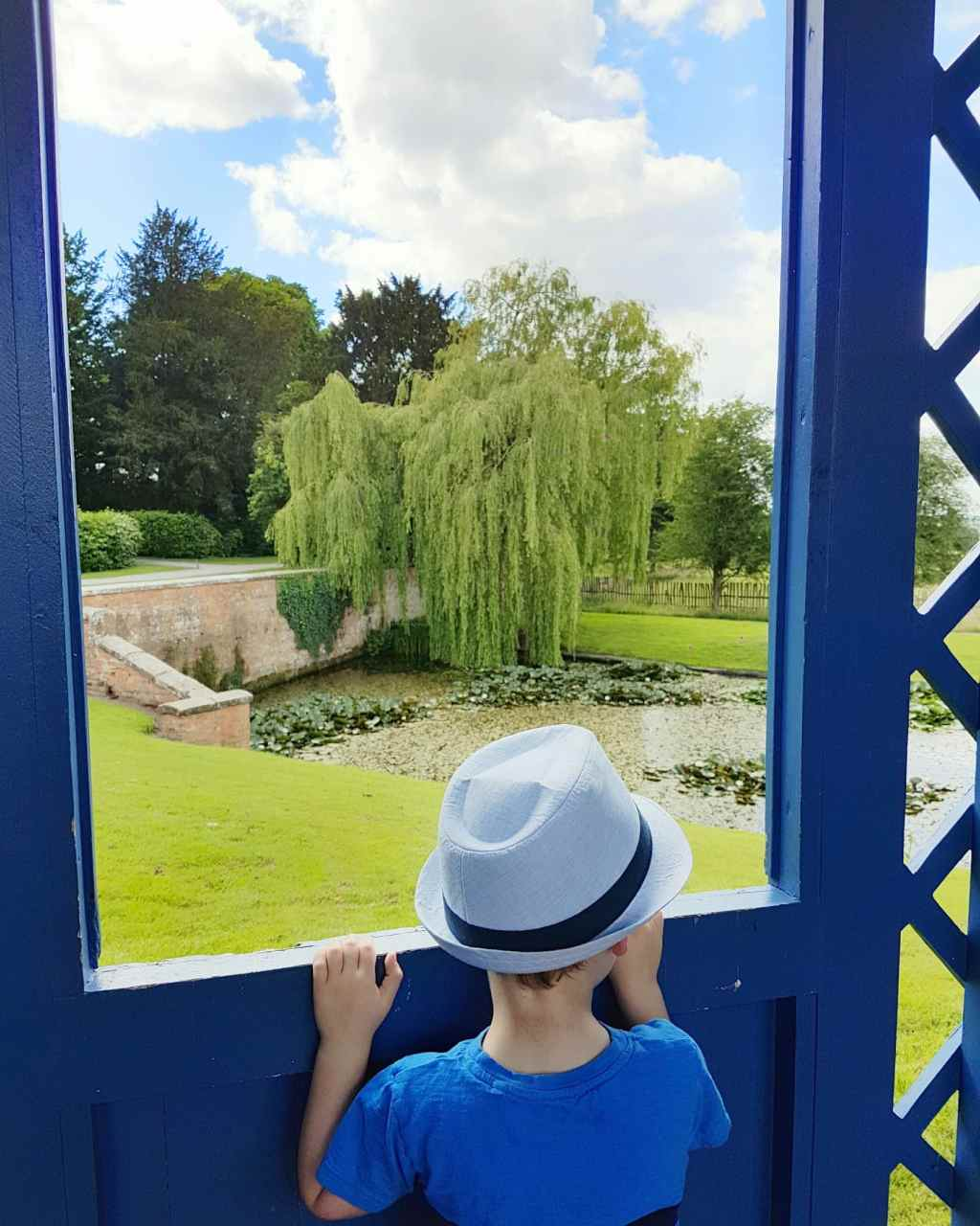 Boy looks out through doorway at pond and willow tree