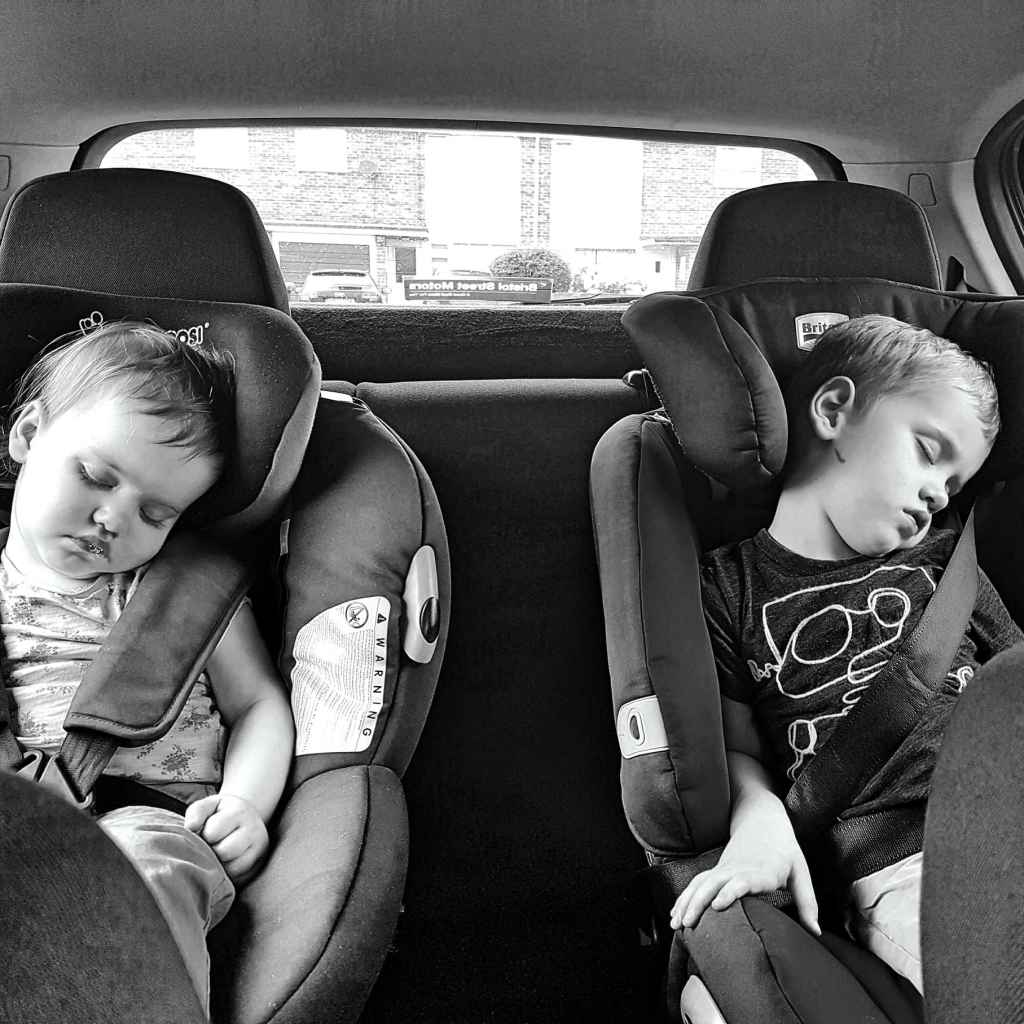 Black and white photo of small girl and small boy asleep in car seats by Someone's Mum