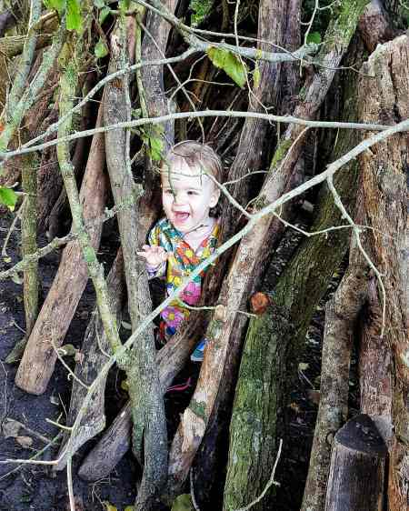 Girl hiding in a stick sculpture while treasure hunting with the Peril Wild Explorers App by Someone's Mum