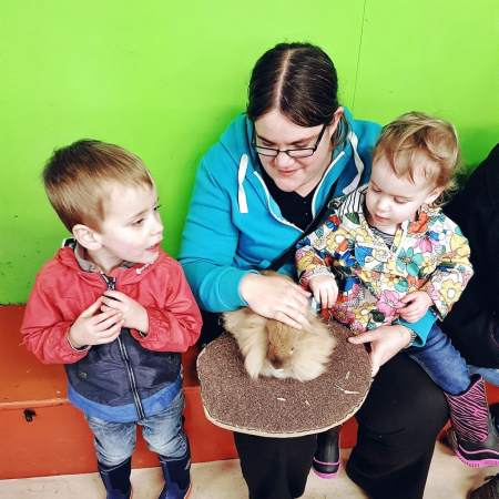 Someone's Mum wither her daughter and her son, stroking a rabbit. Sponsored content allows her to spend more time with her family.