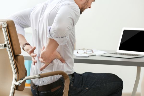 man sitting at a desk and holding his lower back in pain