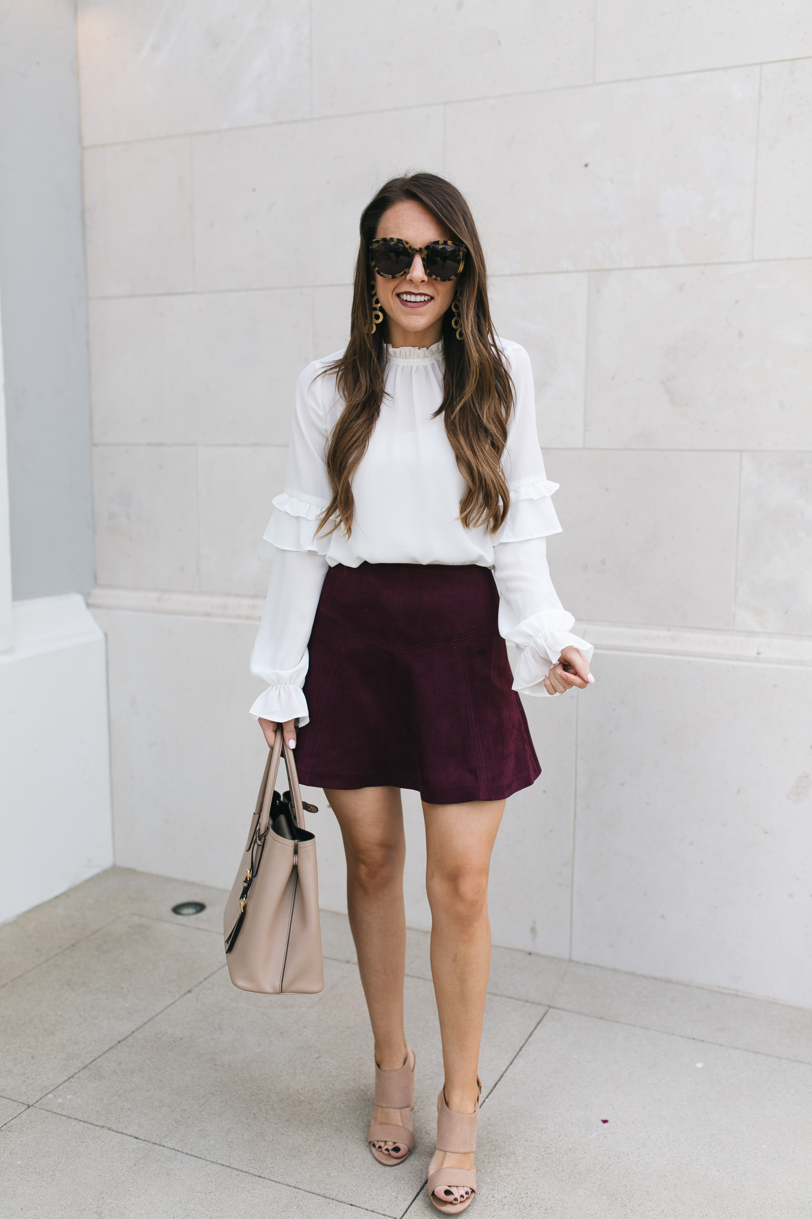 Style blogger Daryl-Ann Denner styles burgundy suede skirt with white ruffle sleeve blouse and shares best suede skirts fall 2017