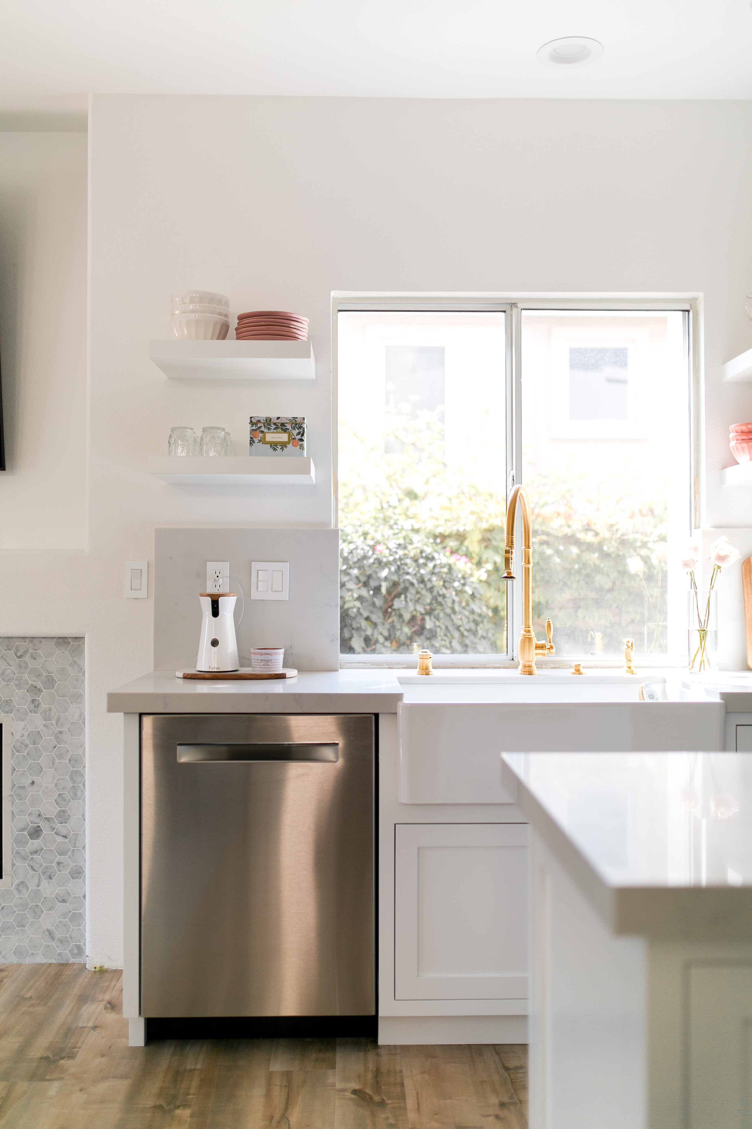 daryl-ann denner reveals her white marble kitchen with open shelving and gold faucet