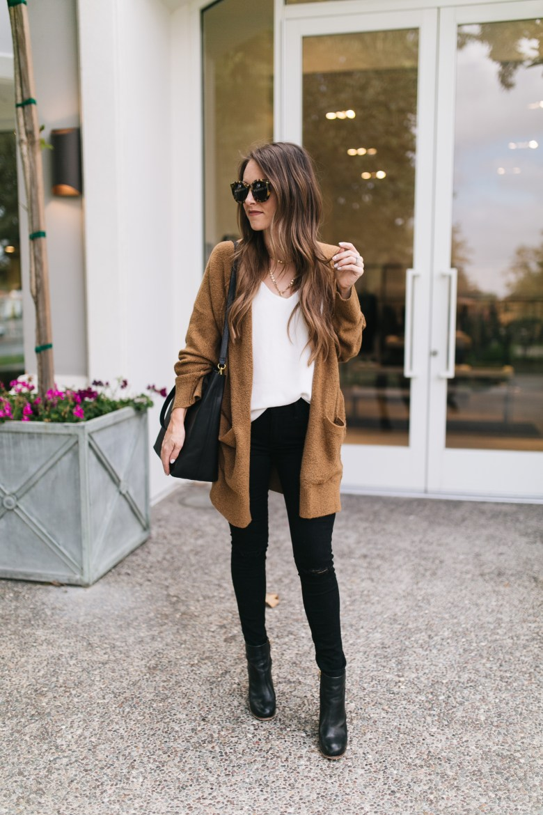 Style blogger Daryl-Ann Denner shares a transitional fall outfit featuring a cozy camel cardigan and black denim with booties and baublebar layered necklace