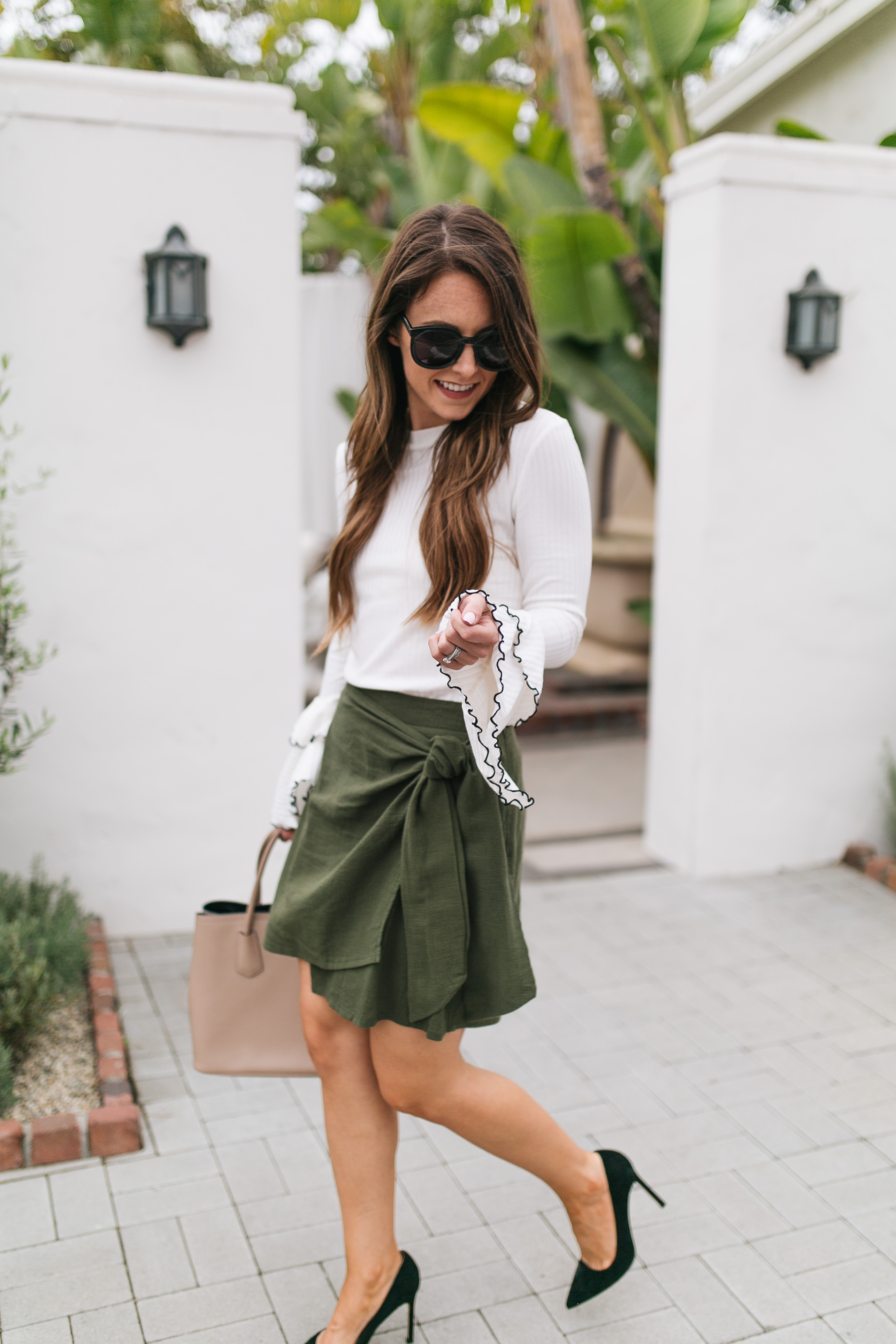 Style blogger Daryl-Ann Denner shares tips on maximizing your work wardrobe and styles an olive wrap skirt and bell sleeve long sleeve tee with black punps