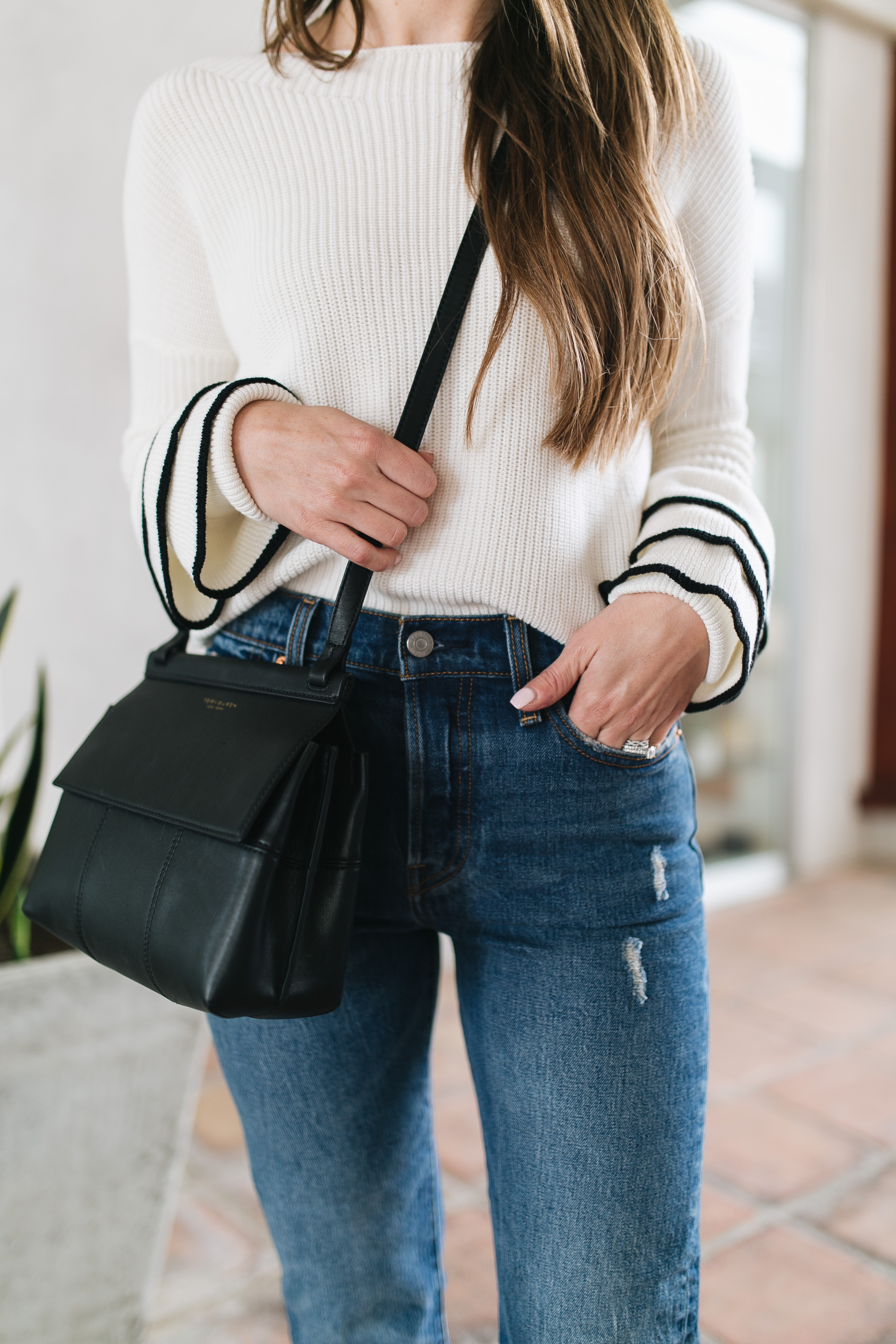 Style blogger Daryl-Ann Denner shares a huge trend for Fall 2017, the ruffle sleeve sweater, and styles an outfit with Levi's and Tory Burch bag