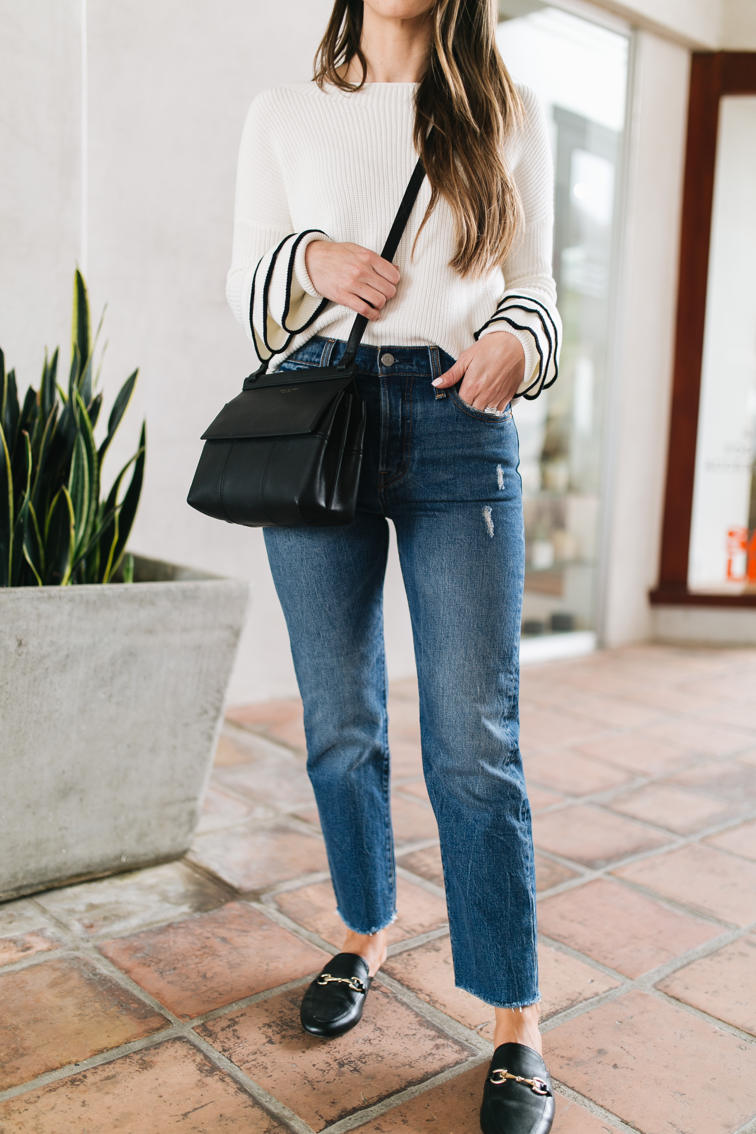 Style blogger Daryl-Ann Denner shares a huge trend for Fall 2017, the ruffle sleeve sweater, and styles an outfit with Levi's and Gucci mules