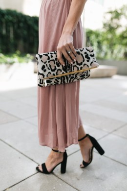 Style blogger Daryl-Ann Denner shares ideas on what to wear to a fall wedding as a guest for under $100 and styles a blush pink midi dress with black heels with clare viver leopard clutch