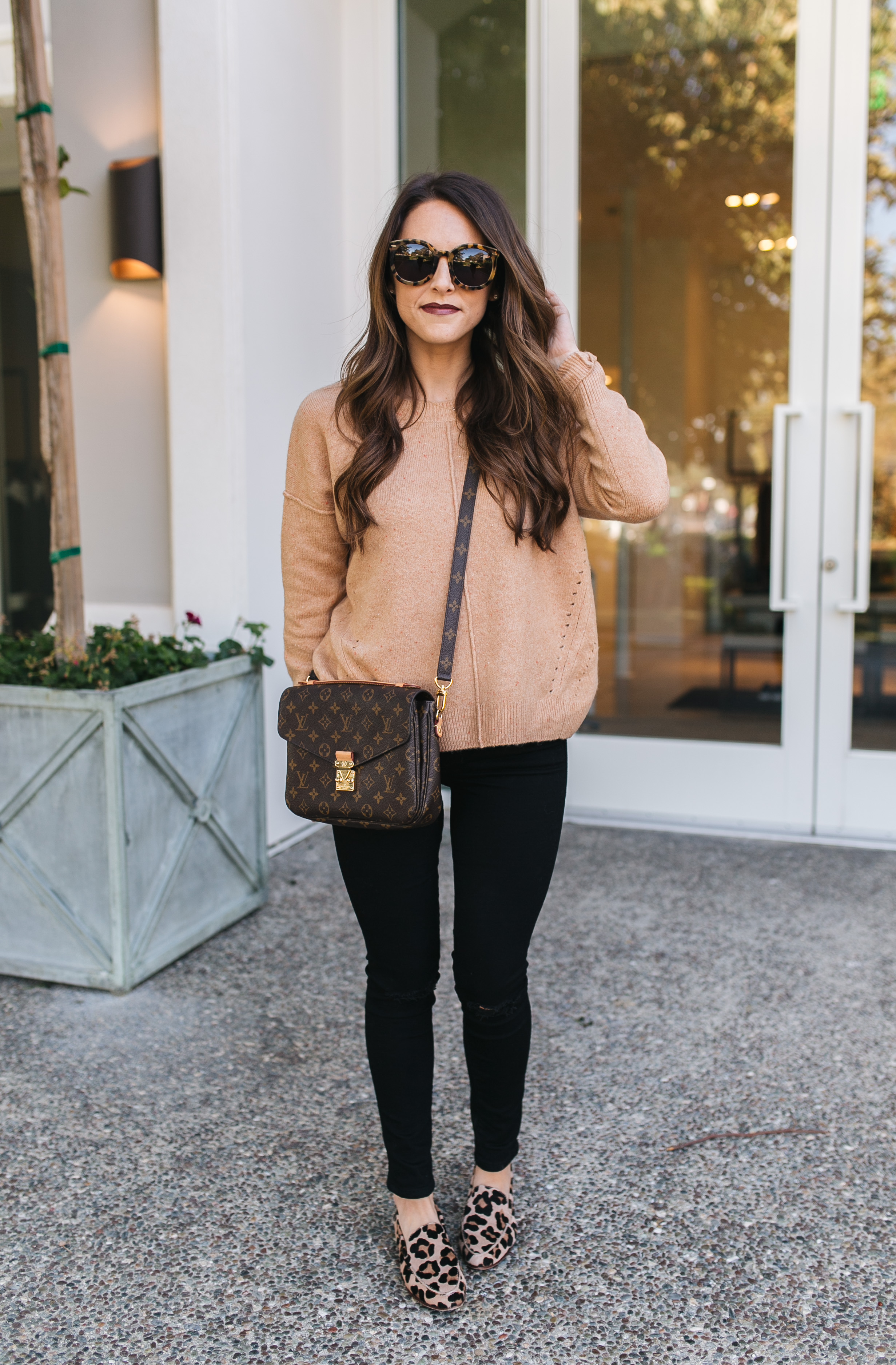 Fashion blogger Daryl-Ann Denner styles a Fall outfit with a Topshop camel sweater, black jeans, and leopard flats, and louis vuitton bag