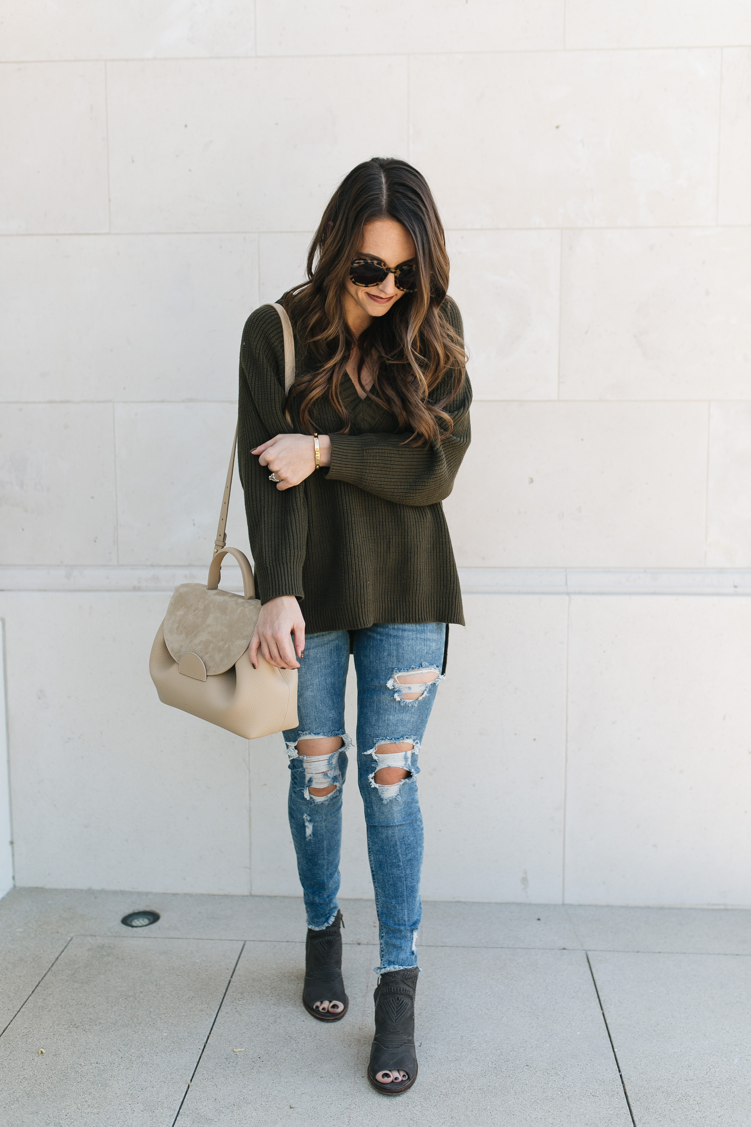 Fashion blogger Daryl-Ann Denner style olive v-neck sweater with ripped skinny jeans and cartier bangle dupe