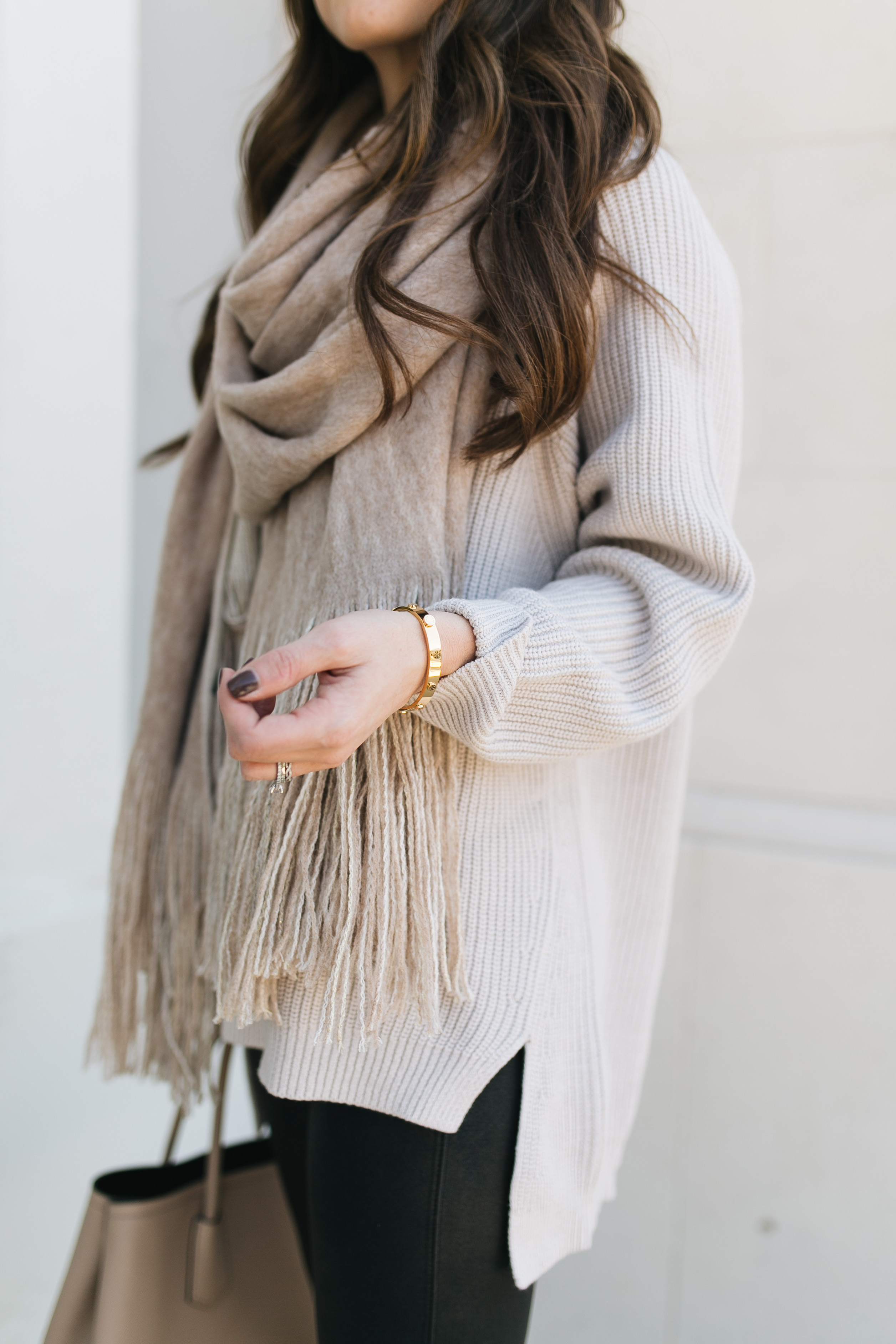 Fashion blogger Daryl-Ann Denner styles oatmeal tunic sweater with faux leather leggings and fringe scarf and cartier love bracelet dupe