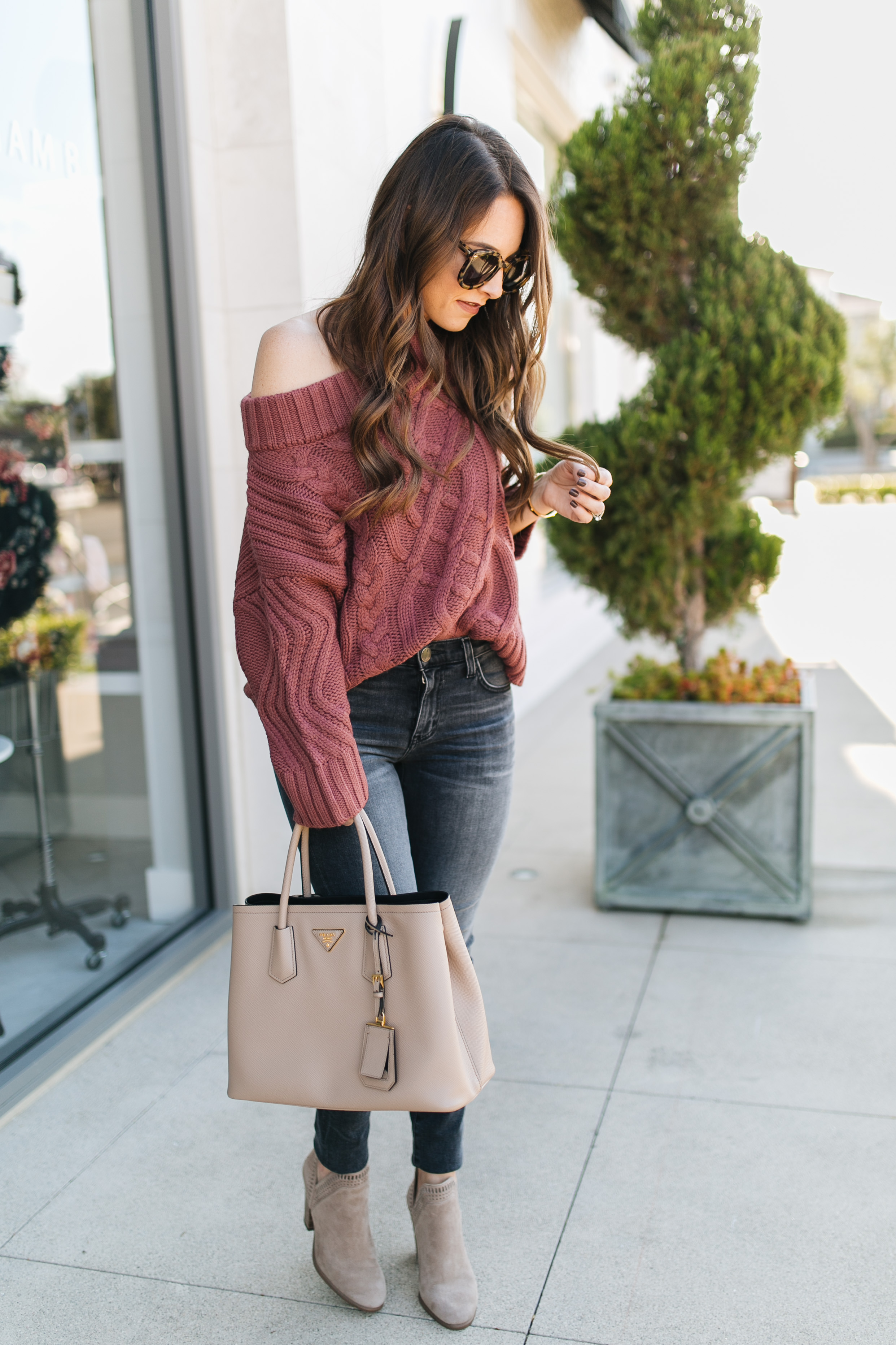 Fashion blogger daryl-ann denner styles a fall outfit with off-the-shoulder sweaters and gray jeans
