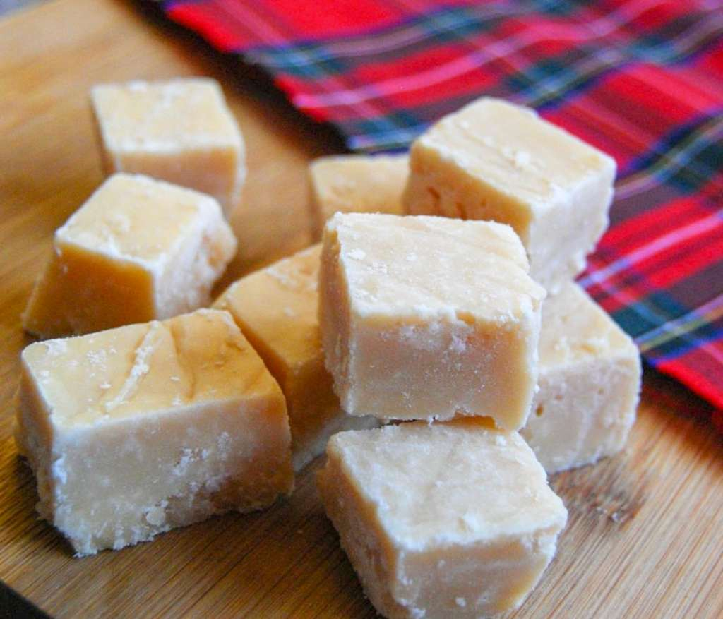 Pieces of Scottish tablet on a wooden board and a tartan blanket in the background.
