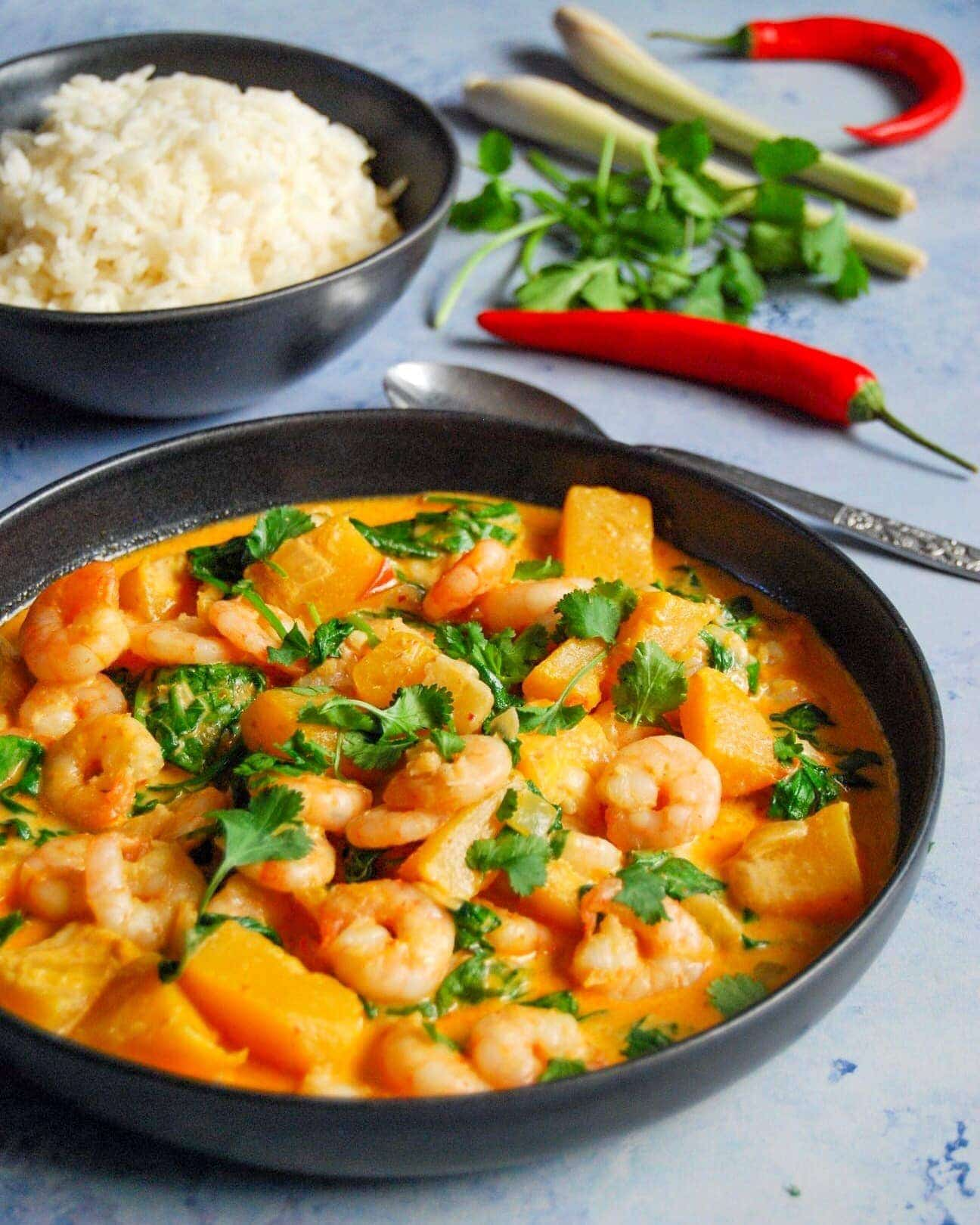 A bowl of Thai red curry with prawns, pumpkin, spinach sprinkled with chopped coriander with a bowl of rice in the background.