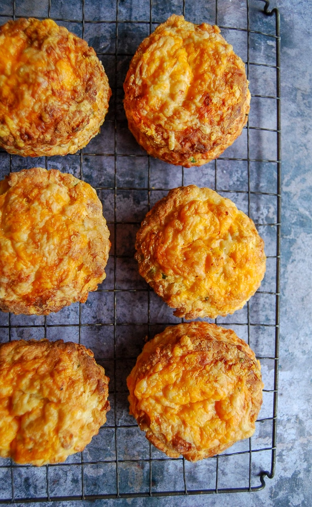 A flatlay close up photograph of six cheese scones on a black wire cooling rack.