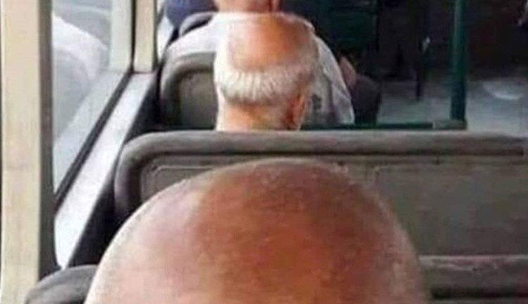 bald men sitting behind each other on bus