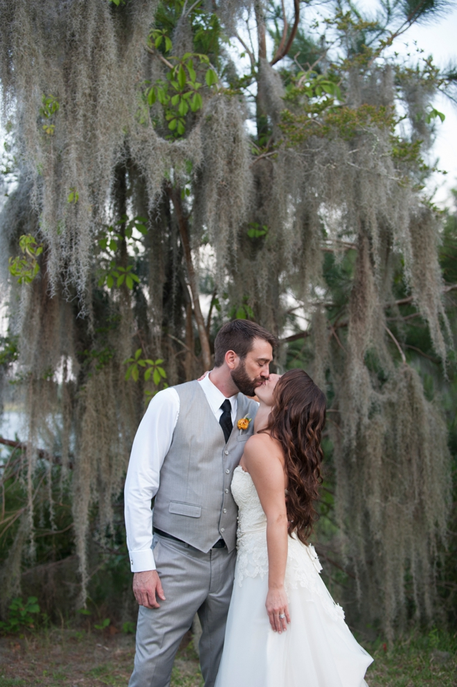 bride and groom kissing under giant tree