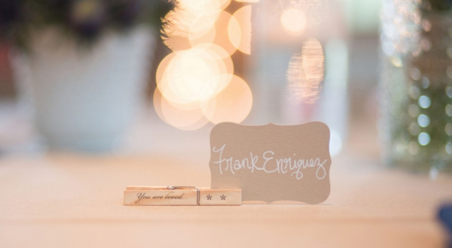 Handwritten seating cards held up by a clothespin