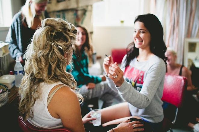 Bridesmaid doing the brides makeup
