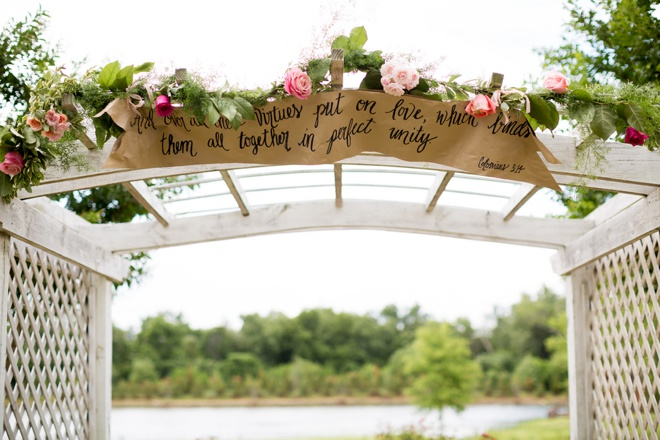 Amazing scripture sign hanging on the ceremony arch.