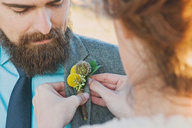 Bride pinning the Grooms boutonniere on him.