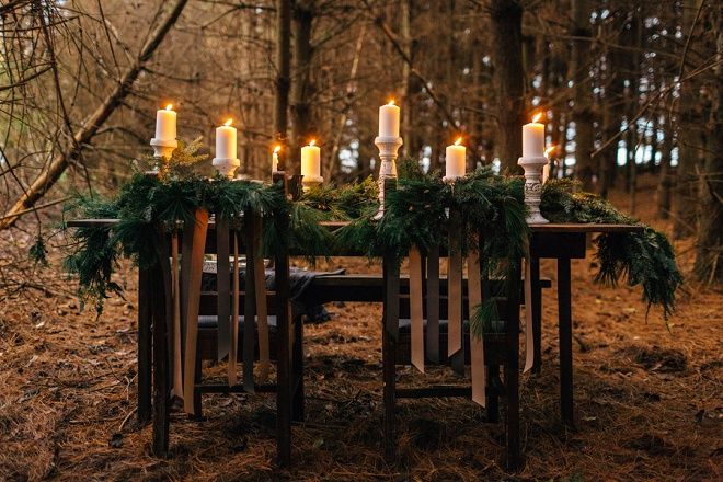 Gorgeous candle lit romantic table in the forest