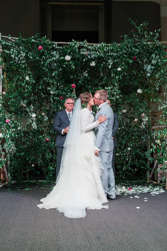 We're loving the gorgeous greenery and floral backdrop behind this gorgeous wedding ceremony