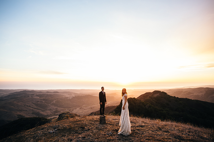 Stunning shot of the bride and groom on a cliff after their wedding, by JD Hudson