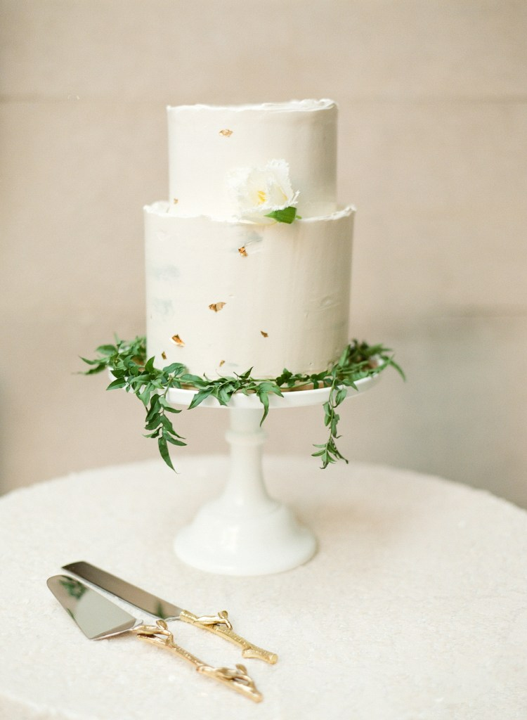 There's something special about this minimalist wedding cake with gold flecks and greenery. So classic.