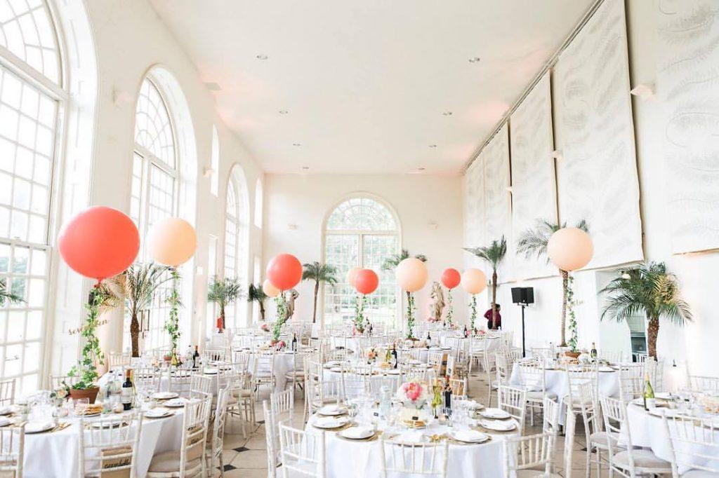 Casamento tropical de palmeiras! Ame os balões usados como números de mesa e o coral.