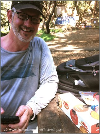 Man wearing glasses at picnic table with backpack