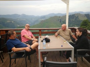 Three men and a young woman on a deck overlooking the Pyrenees