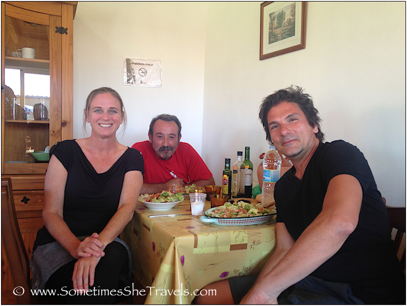 A Woman and two men at a table full of food