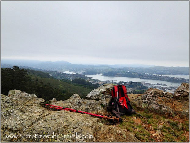 backpack and poles on rocks with view of bay